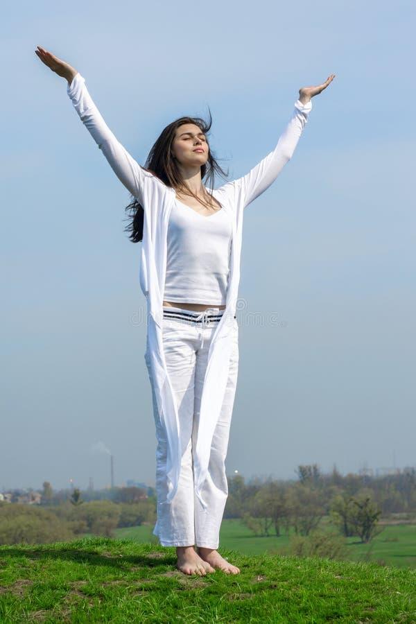 Flicka som gör yogaövningsanseende på en kulle royaltyfria foton