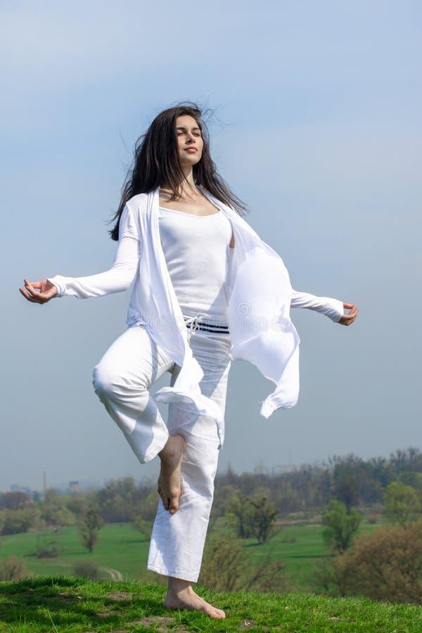 Flicka som gör yogaövningsanseende på en kulle royaltyfri fotografi
