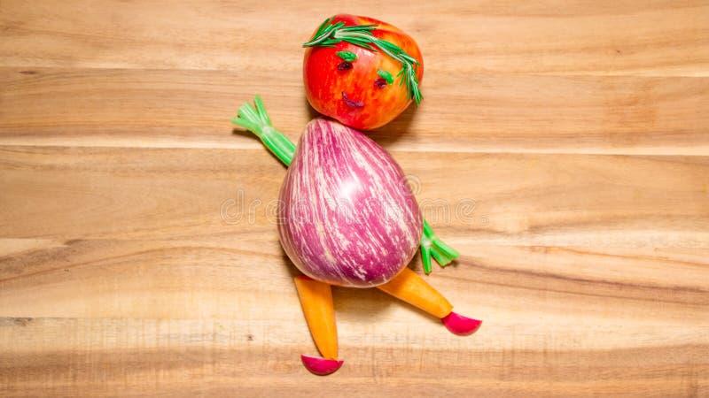 Flicka som göras av auberginefrukt- och grönsakdanser på skärbräda arkivbild