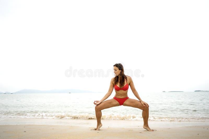 Flicka som g?r yoga p? stranden royaltyfri foto