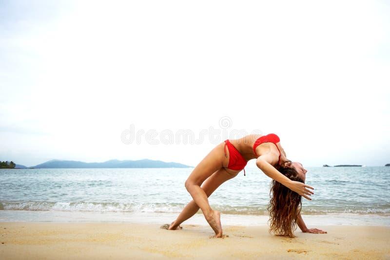 Flicka som g?r yoga p? stranden royaltyfri bild