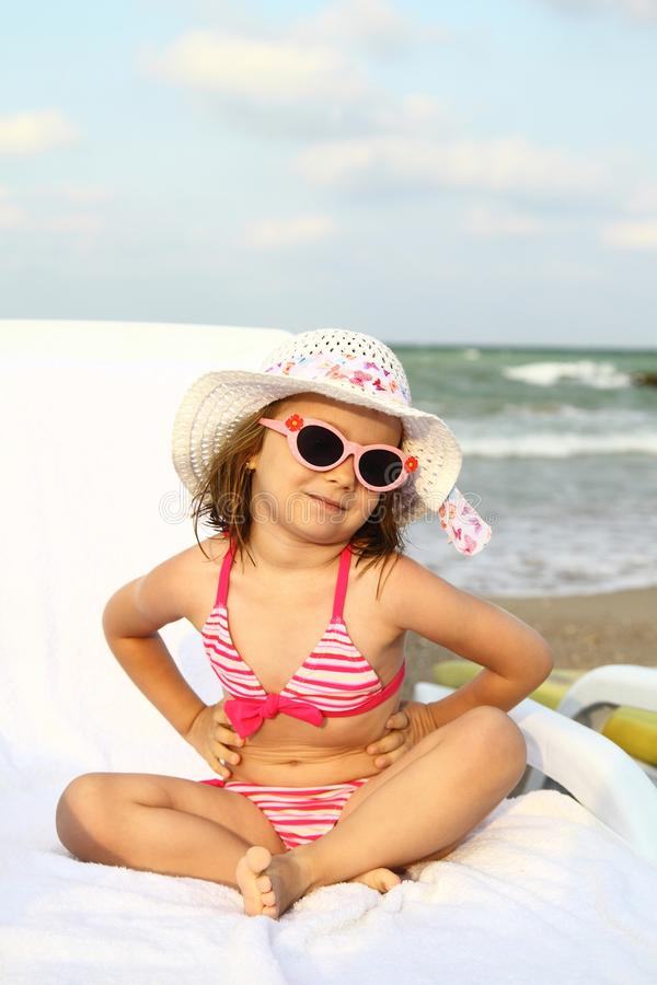 Flicka som garvar på sunbed på stranden royaltyfri bild