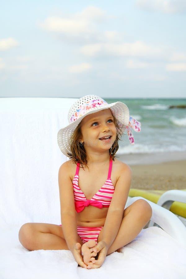 Flicka som garvar på sunbed på stranden fotografering för bildbyråer