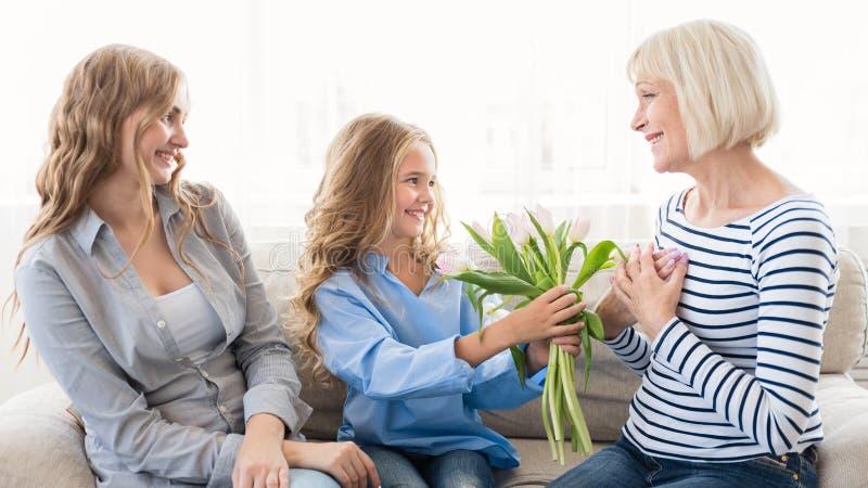 Flicka som ger buketten av tulpan till hennes farmor royaltyfri bild