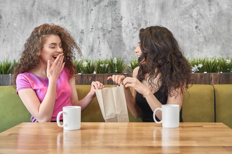 Flicka som ger gåva till den förvånade vännen i kafé arkivfoton