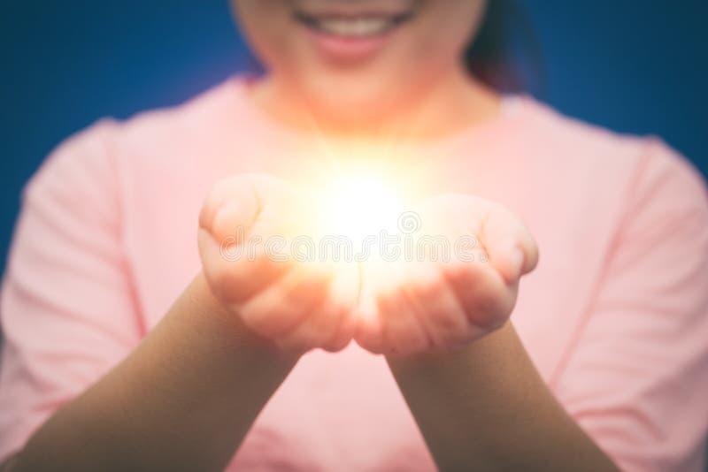 Flicka som ger mirakel eller hopp i henne händer royaltyfri foto