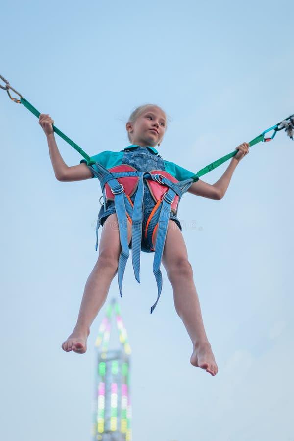 Flicka som hänger på rubber remmar på bakgrunden av ett glödande torn Den stärkande ritten arkivbilder