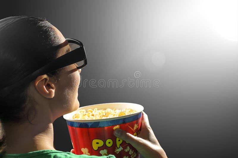 Flicka som håller ögonen på bion 3D arkivfoton