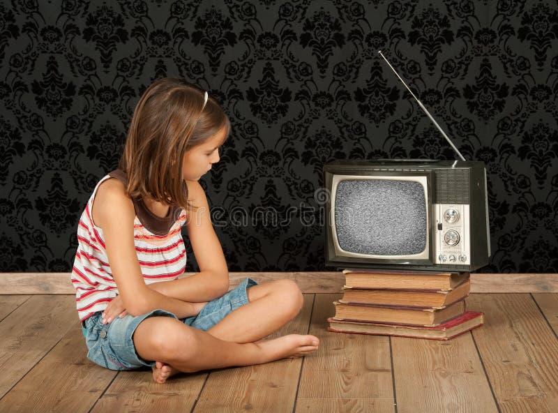 Flicka som håller ögonen på den gammala tv:n royaltyfri bild
