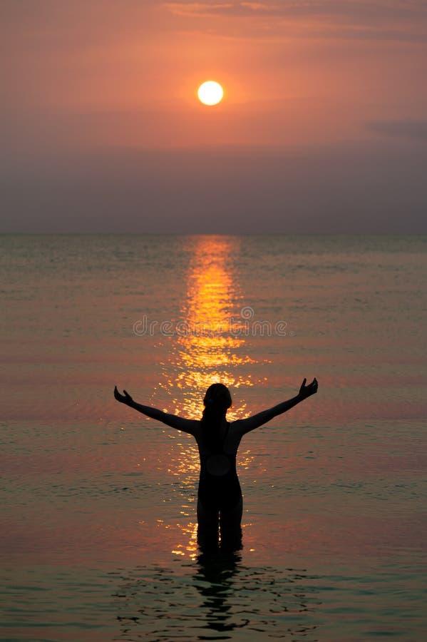Flicka som håller ögonen på den härliga reflekterade modellen av solen som en trappuppgång på brand fotografering för bildbyråer
