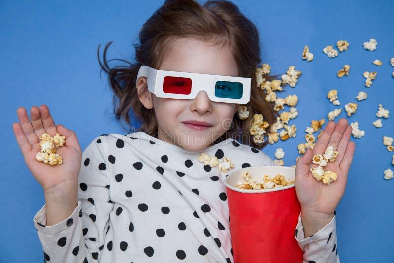 Flicka som håller ögonen på en film i exponeringsglas 3D med popcorn royaltyfri foto