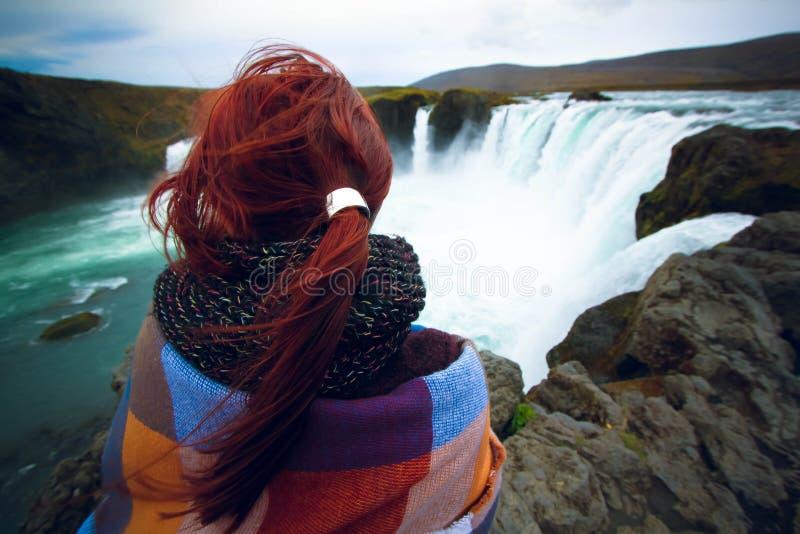 Flicka som håller ögonen på på den Godafoss vattenfallet, Island arkivfoton