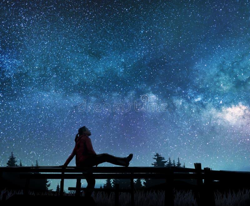 Flicka som håller ögonen på stjärnorna i natthimmel arkivfoto