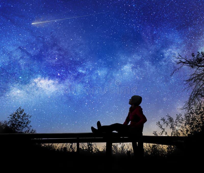 Flicka som håller ögonen på stjärnorna i natthimmel royaltyfri foto
