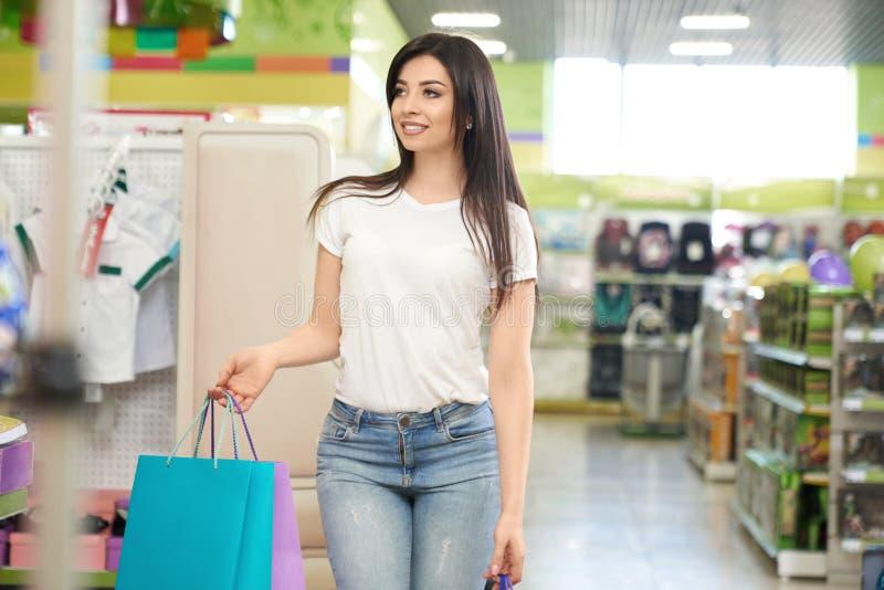 Flicka som håller pappers- påsar och shoppar i supermarket arkivbild