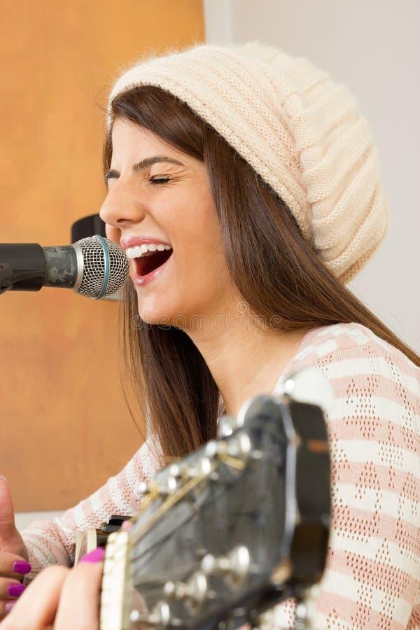 Flicka som högt sjunger och spelar gitarren arkivbild