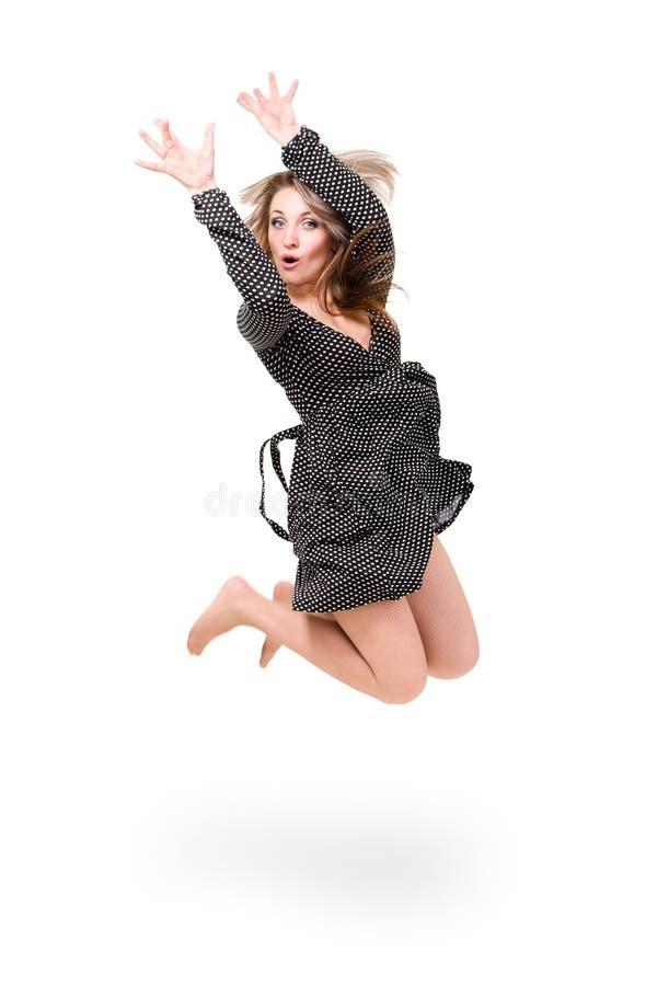 Härlig flicka som ha på sig en klänning som hoppar upp fotografering för bildbyråer