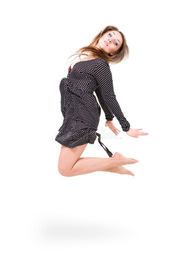 Härlig flicka som ha på sig en klänning som hoppar upp arkivfoton