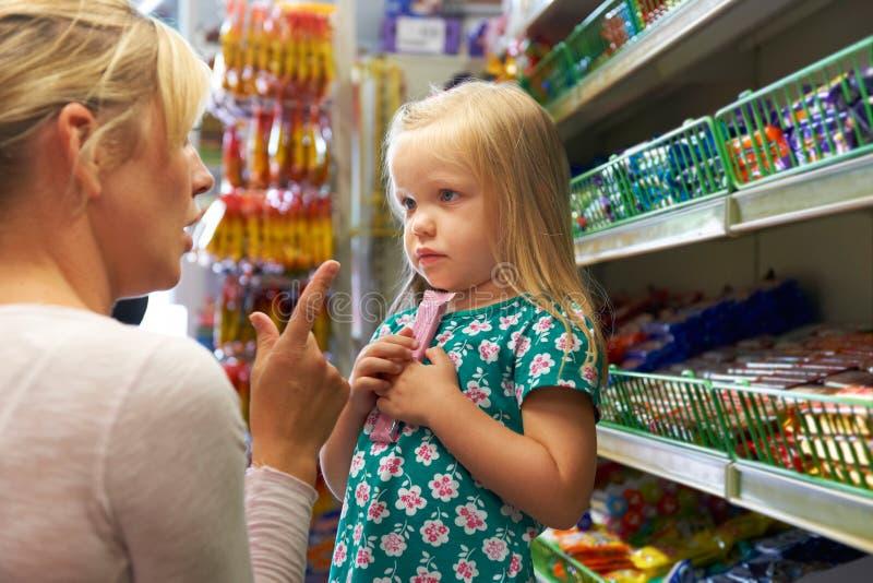 Flicka som har argument med modern på godisräknaren i Supermarke royaltyfri fotografi