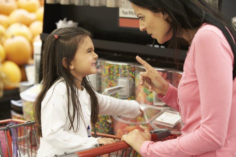 Flicka som har argument med modern på godisräknaren i supermarket royaltyfri fotografi