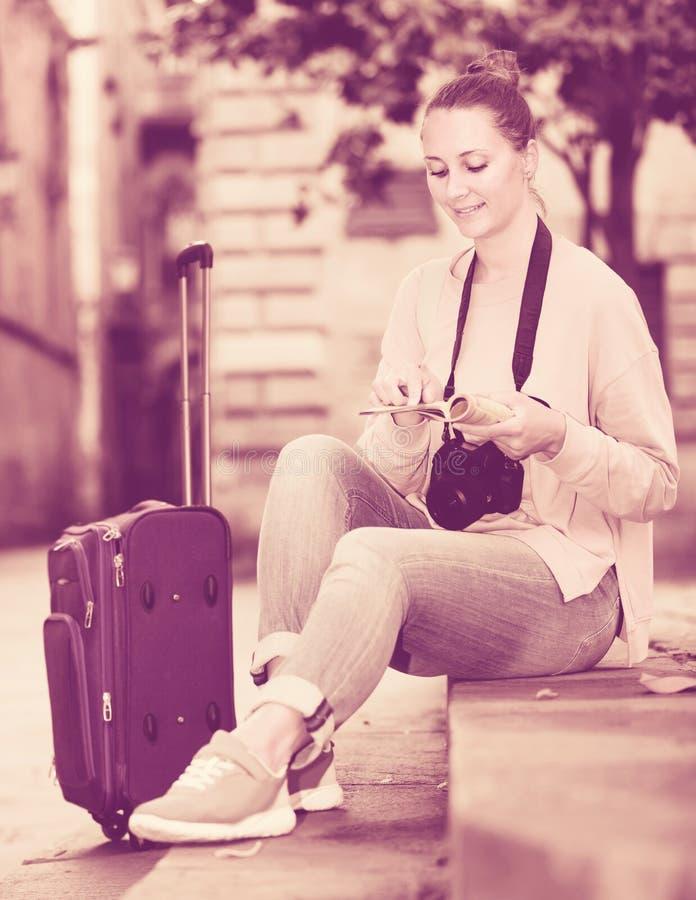 Flicka som har broschyren och söker efter hennes rutt i stad royaltyfri foto