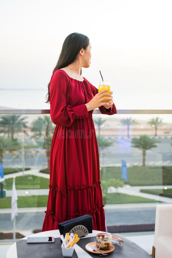Flicka som har en drink på restaurangbalkongen arkivfoto