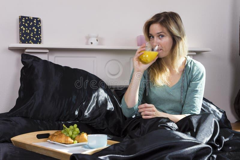 Flicka som har frukosten i säng arkivfoto