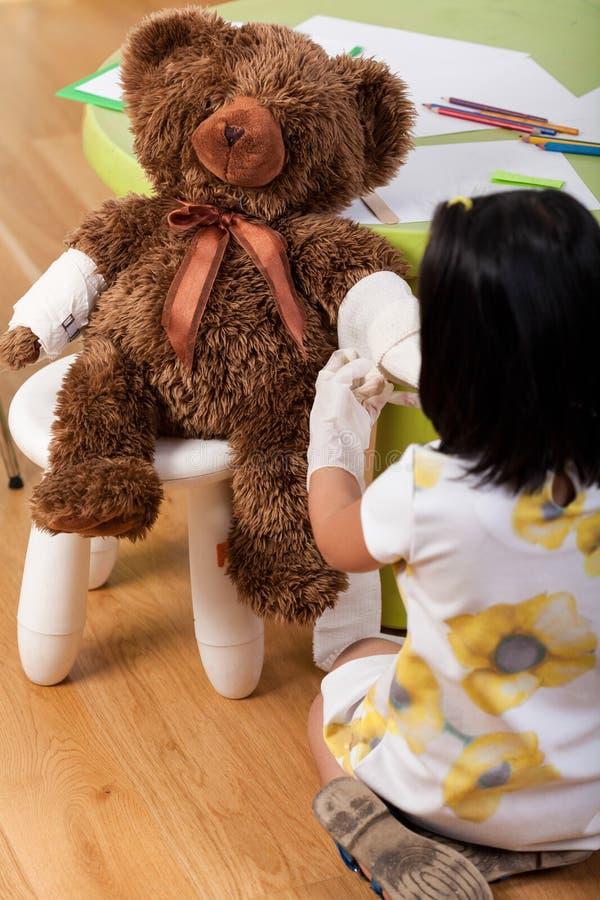 Flicka som har gyckel med nallebjörnen royaltyfri bild