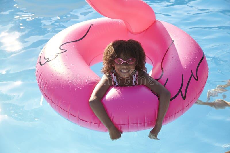 Flicka som har gyckel med uppblåsbar i utomhus- simbassäng royaltyfria foton