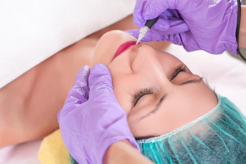 Flicka som har permanent makeup på kanter i kosmetologsalong arkivbild