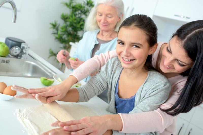 Flicka som har rolig bakning med farmodern och mumen royaltyfria bilder