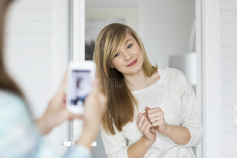Flicka som hemma fotograferar systern till och med den smarta telefonen royaltyfria bilder