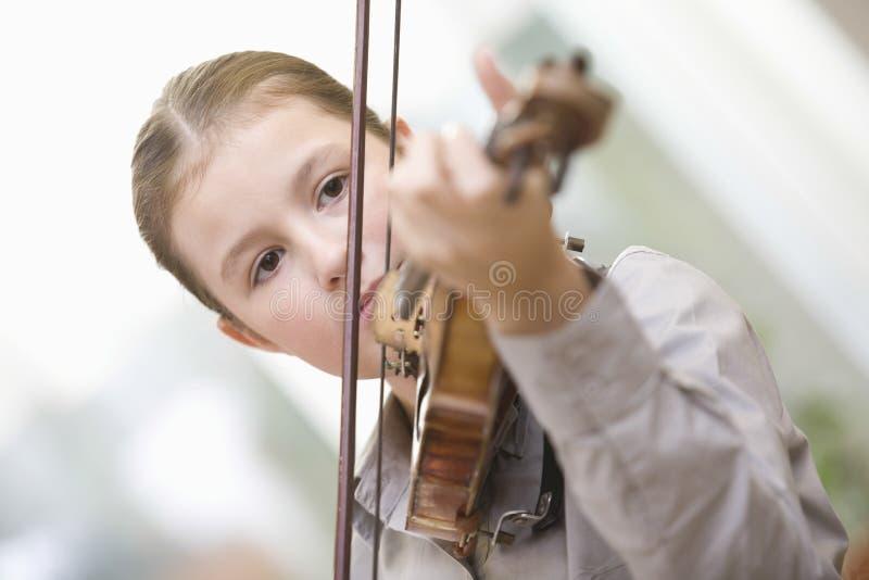 Flicka som hemma spelar fiolen arkivbilder