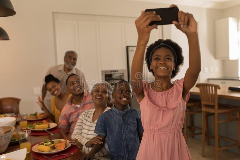 Flicka som hemma tar selfie av familjen med mobiltelefonen på den äta middag tabellen royaltyfri fotografi