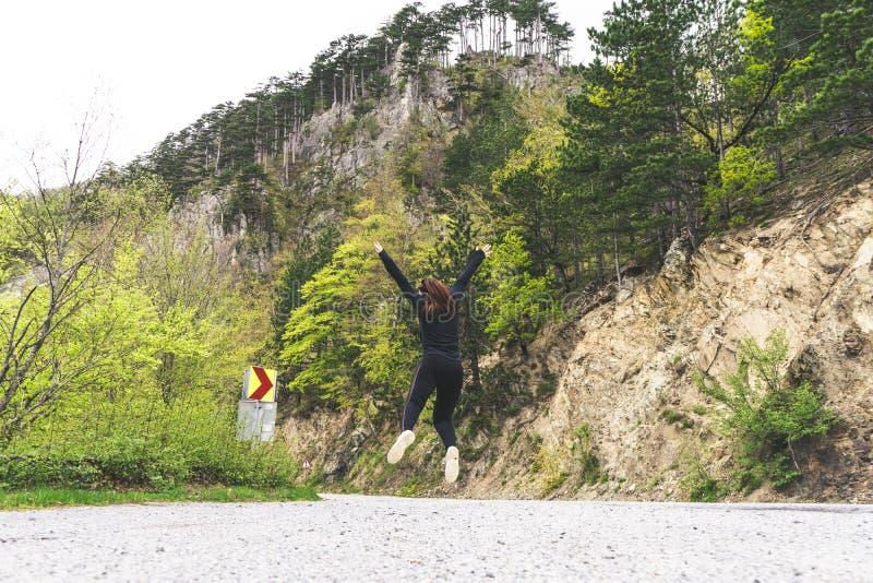 Flicka som hoppar i mitt av vägen i en nationalpark Durmitor, Montenegro Det röda huvudet hoppar för lycka och frihet royaltyfri bild