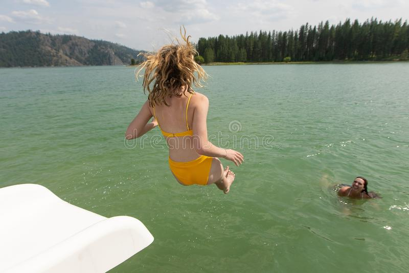 Flicka som hoppar in i sjön från vattenglidbana arkivbild