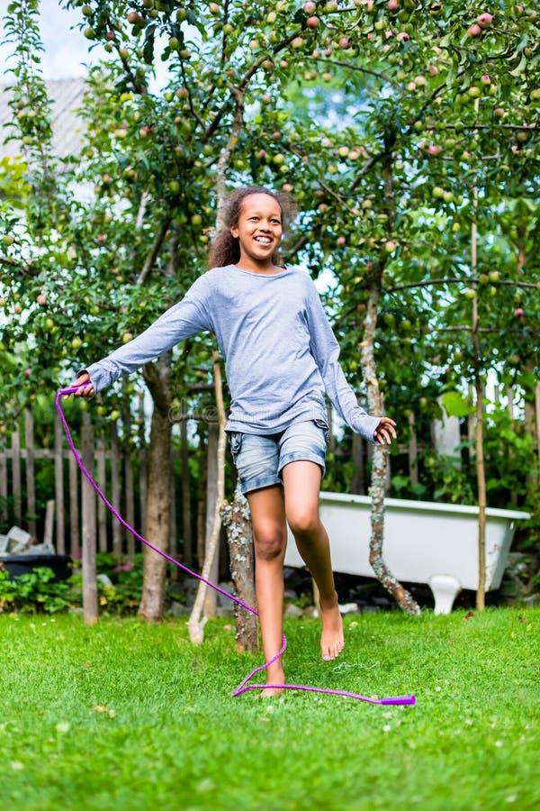Flicka som hoppar over i trädgården royaltyfri bild