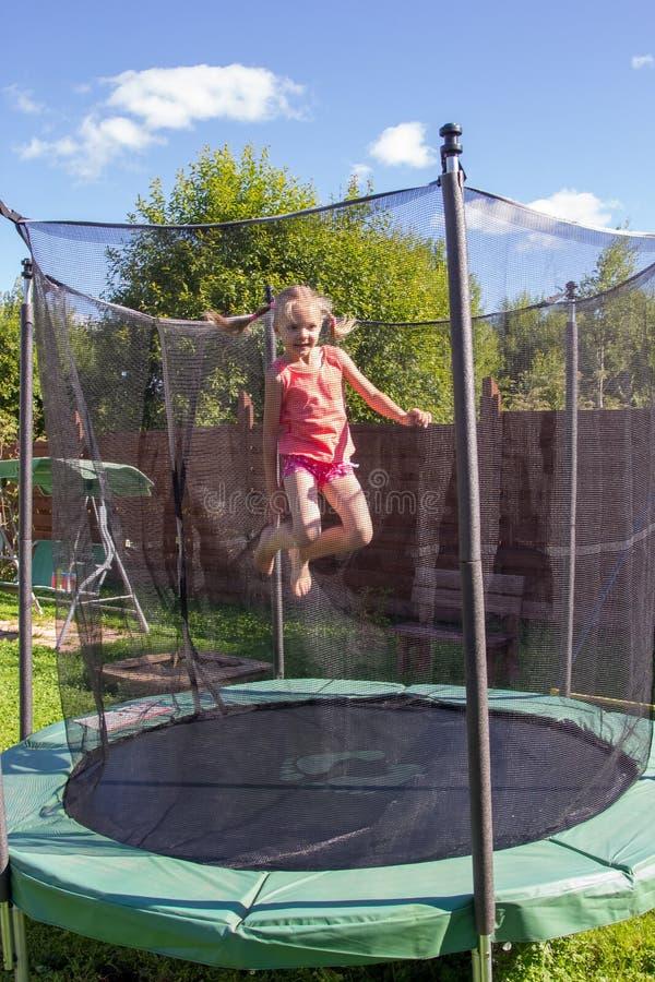 Flicka som hoppar p? en trampolin bak skyddande netto royaltyfria bilder