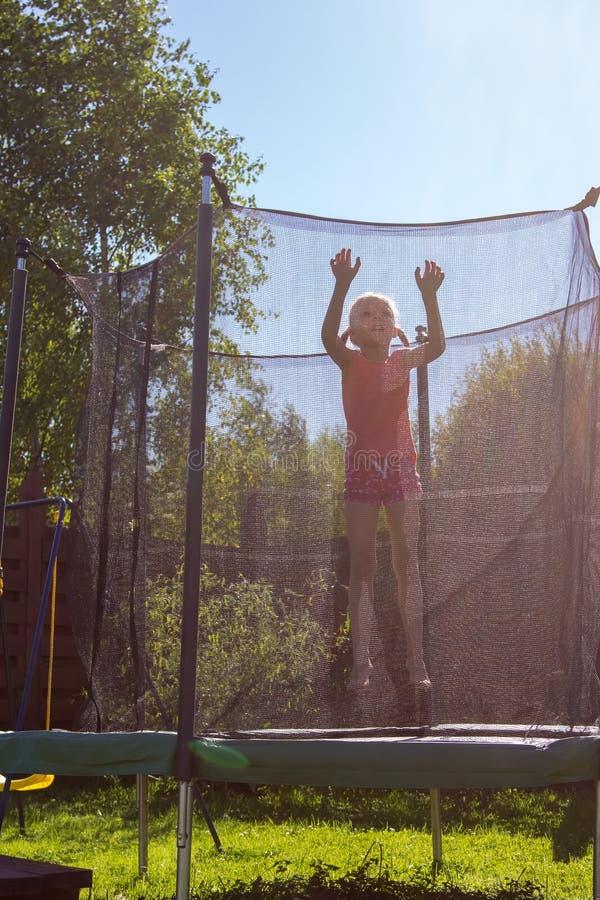 Flicka som hoppar p? en trampolin bak skyddande netto arkivfoton