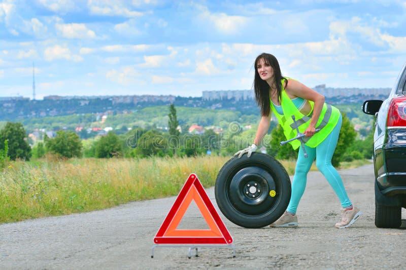 Flicka som hoppas för hjälp med utbytet för extra- hjul Stansat hjul på vägen, medan köra Flicka l i reflekterande väst arkivfoto