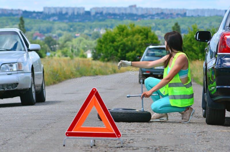 Flicka som hoppas för hjälp med utbytet för extra- hjul fotografering för bildbyråer