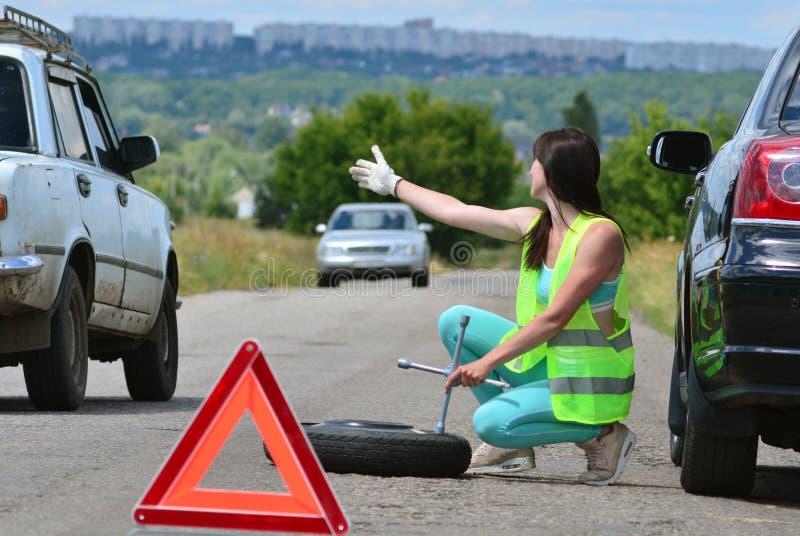 Flicka som hoppas för hjälp med utbytet för extra- hjul Stansat hjul på vägen, medan köra Flicka l i reflekterande väst rymmer hj arkivbilder