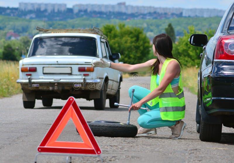 Flicka som hoppas för hjälp med utbytet för extra- hjul Stansat hjul på vägen, medan köra Flicka l i reflekterande väst rymmer hj royaltyfri bild
