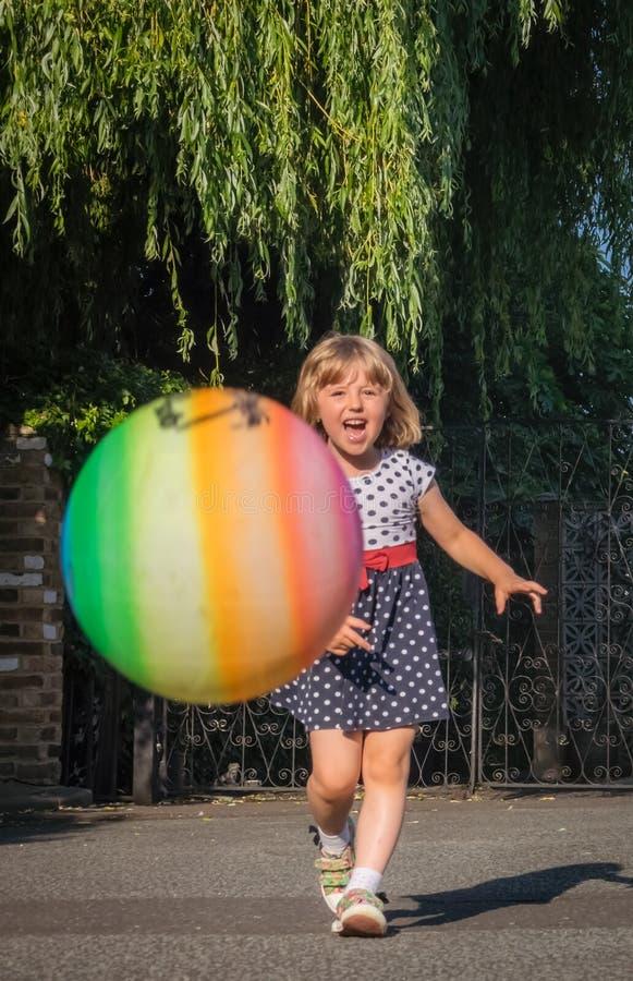 Flicka som jagar bollen arkivbild