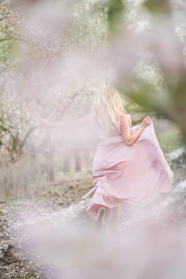 Flicka som kör i en magisk trädgård för fruktblomningvår Konstfoto med den mjuka selektiva fokusen royaltyfria foton