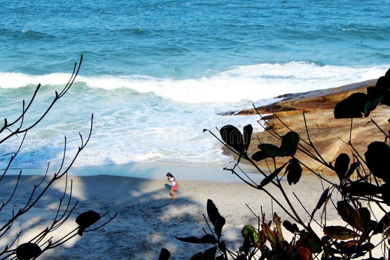 Flicka som kör på sand på stranden royaltyfri bild