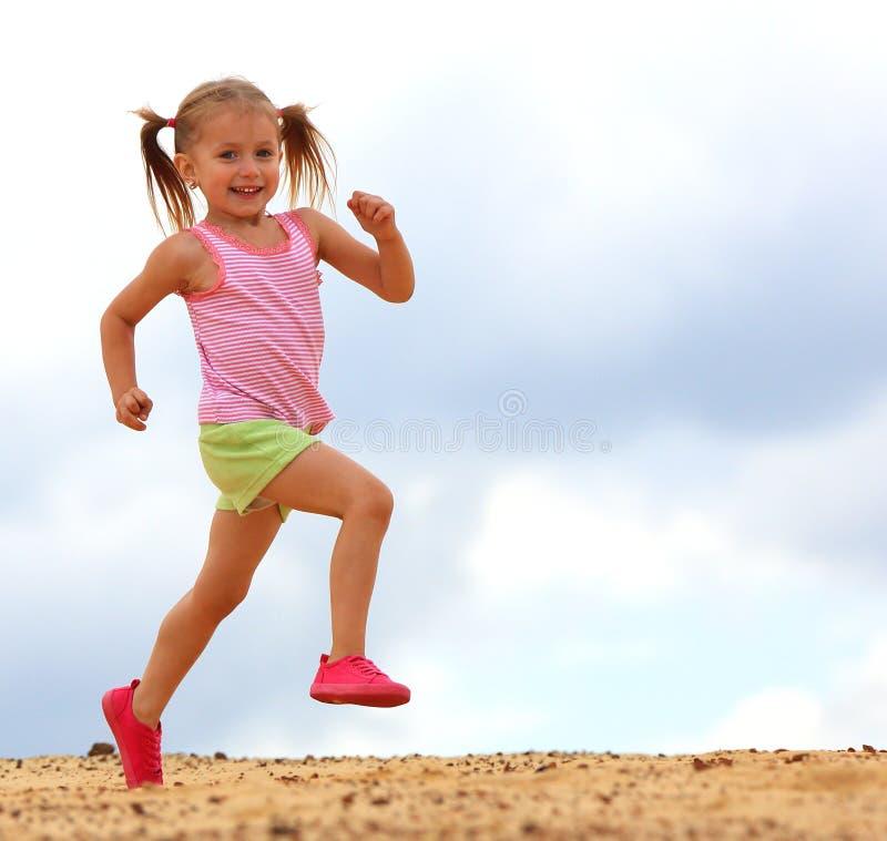 Flicka som kör på strand arkivfoto