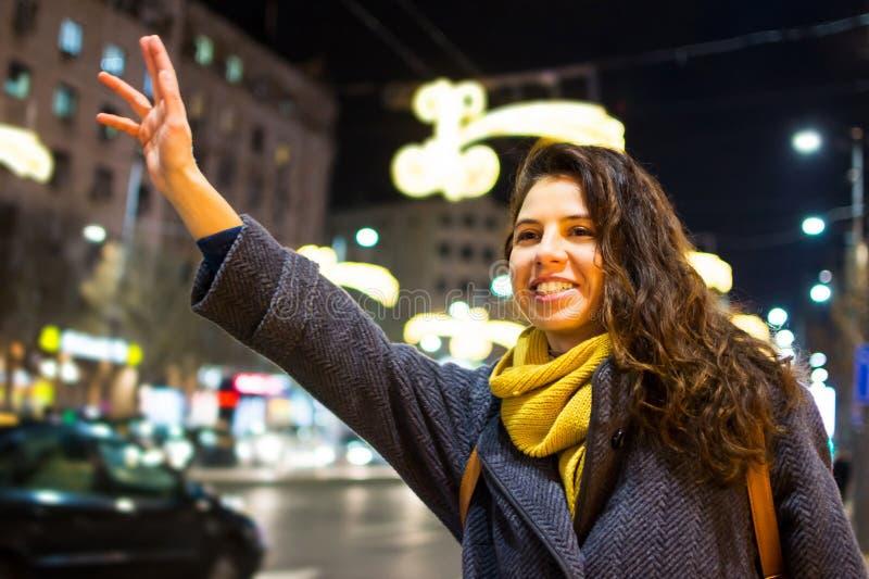 Flicka som kallar taxien i stads- miljö royaltyfria bilder