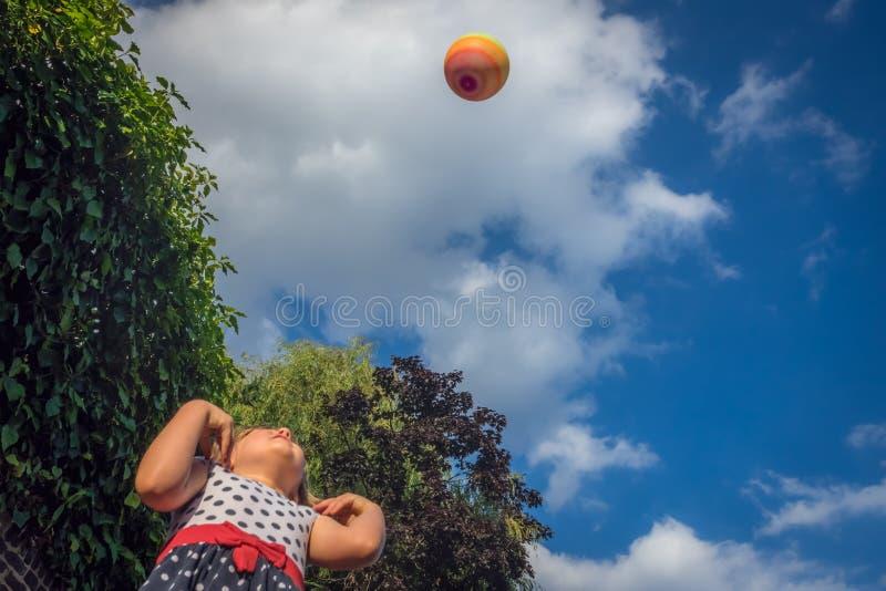 Flicka som kastar och fångar bollen fotografering för bildbyråer