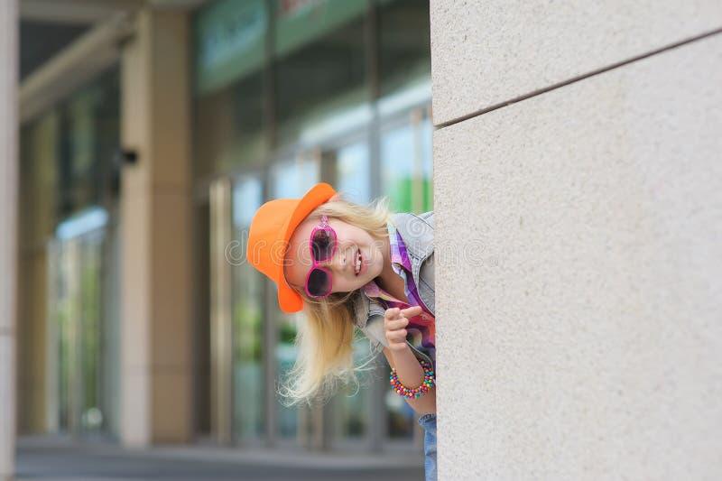 Flicka som kikar runt om hörnet arkivfoton